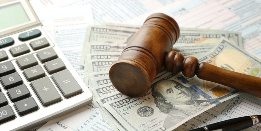gavel calculator and hundred dollar bills representing a lawsuit settlement