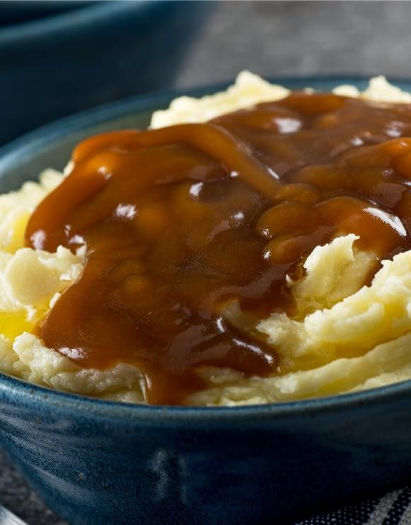 Vegan gravy flowing through swirls of mashed cauliflower