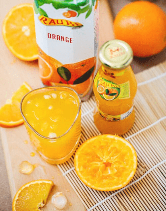 A small glass of orange juice with orange slices lying next to the glass