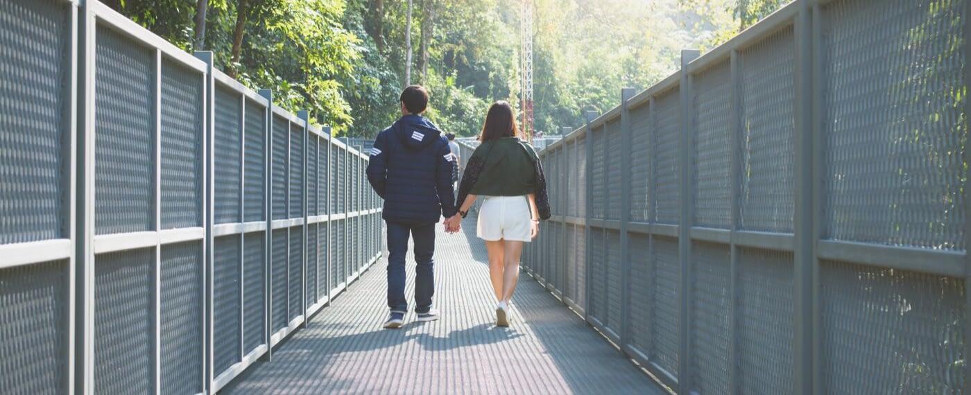 Couple walking hand in hand across a metal bridge