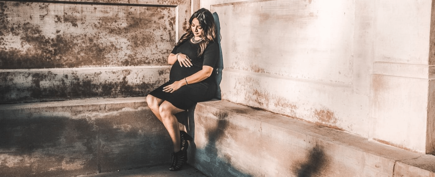 Pregnant woman in black dress sitting on a cement ledge holding her stomach