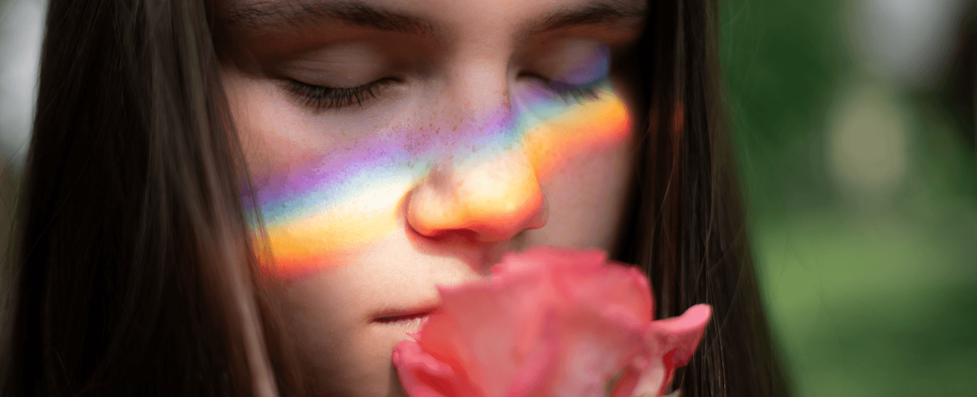 a girl smiling a rose with a light prism across her face