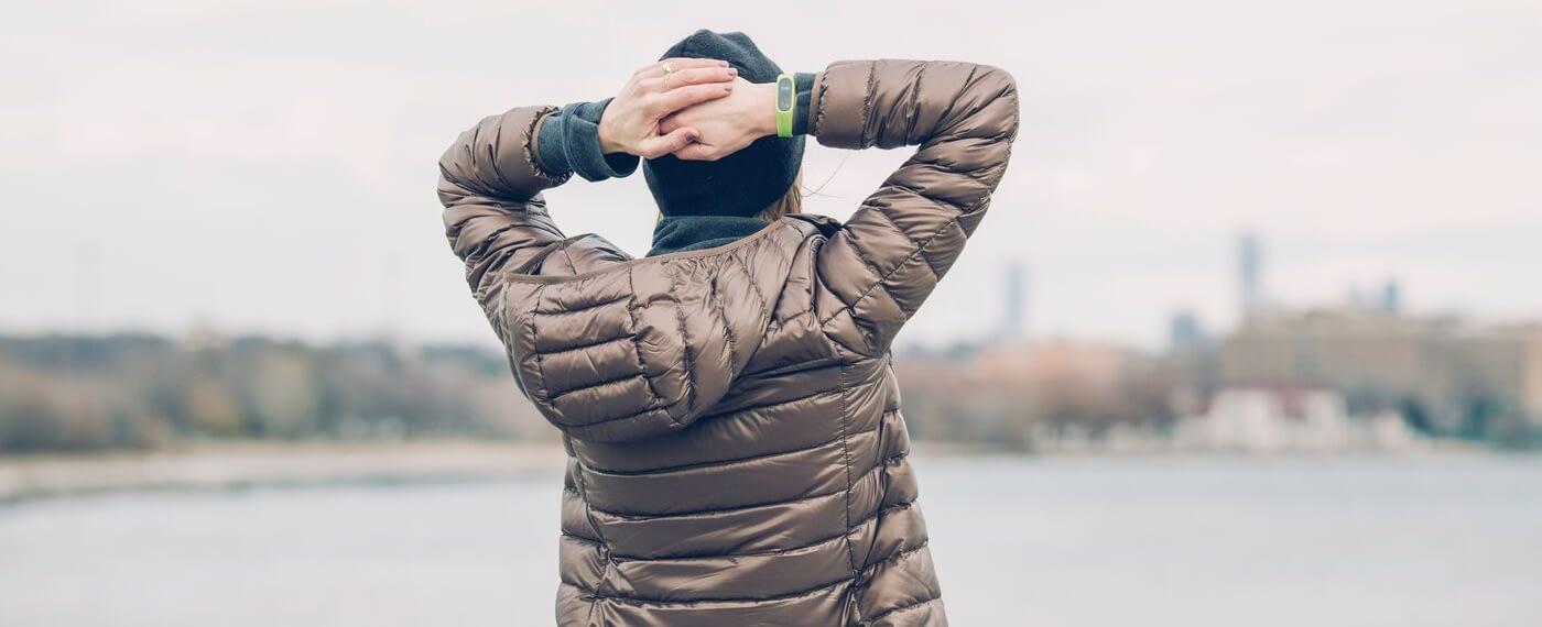 Woman in brown puffy coat looking at lake