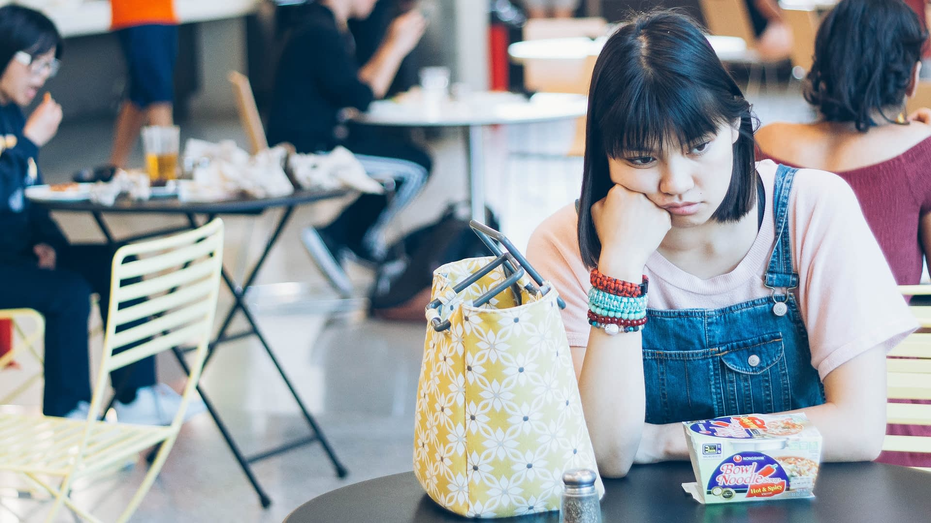 Woman with depressions sits alone at a table pouting