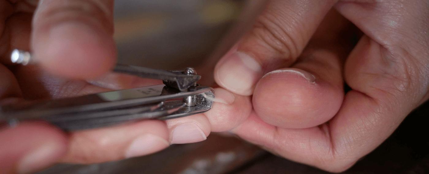 trimming toenails using a nail clipper