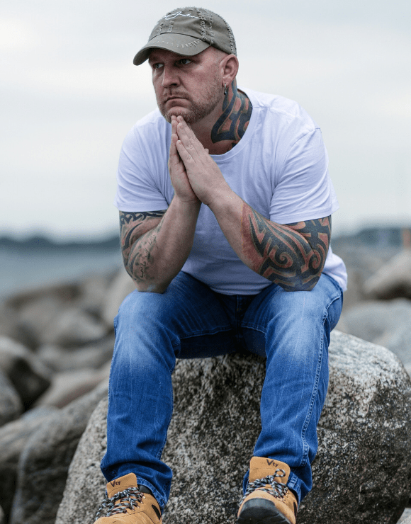 Man sits on top of a large rock thinking about mental health