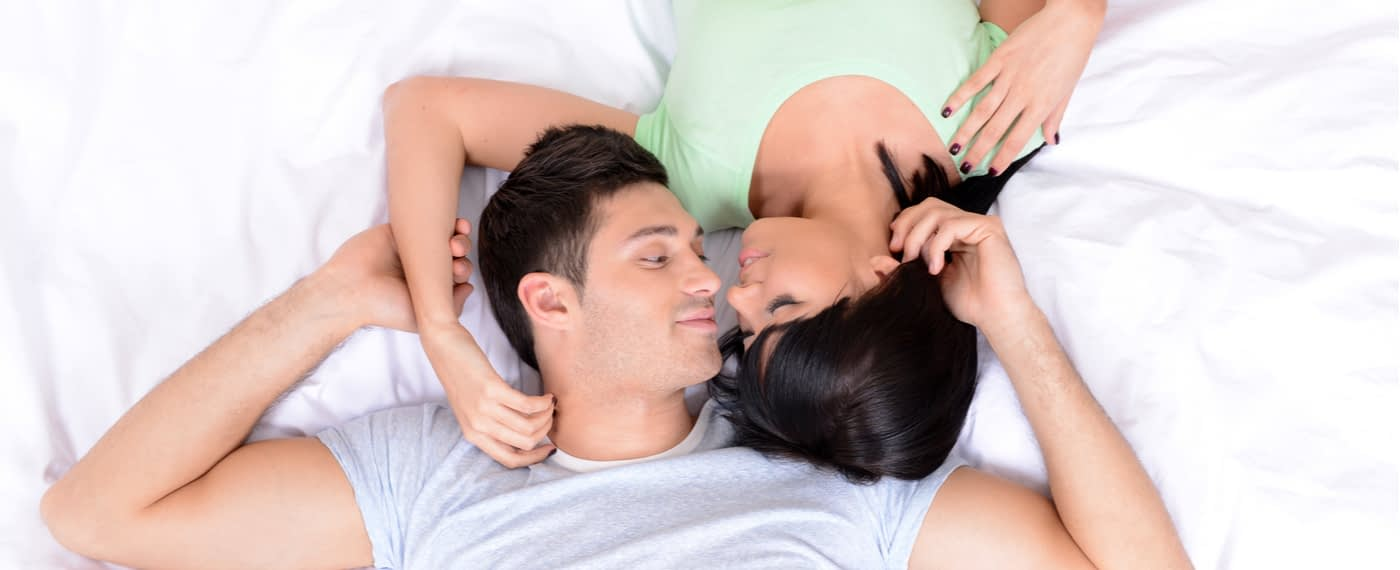 Aerial view of couple laying in bed on white sheets