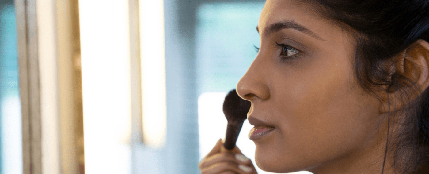 Woman applying blush to her face with makeup brush