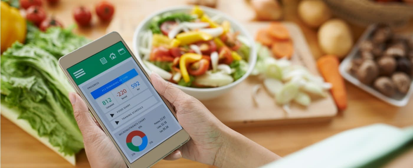 Person holding hone in front of vegetables searching for weight management apps