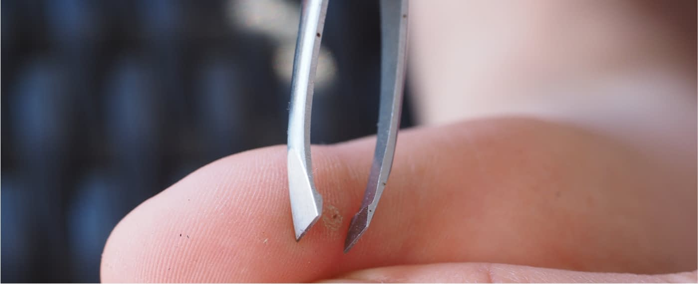 Tweezers being used to pull a splinter from the skin of a finger after using epsom salt