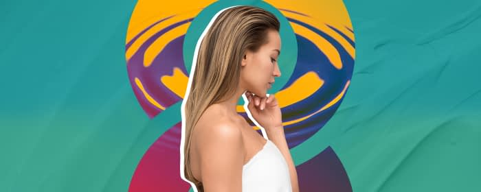 Blonde woman standing in front of teal background