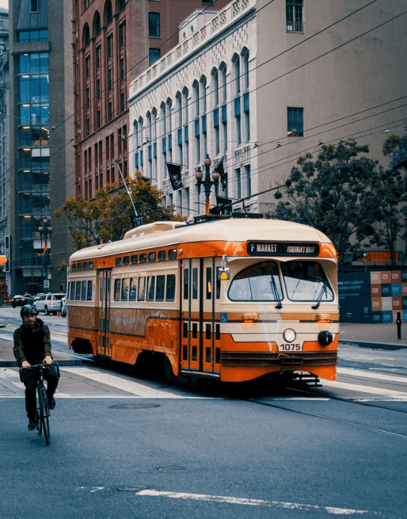 Man riding a bike next to public trans to help promote energy efficiency
