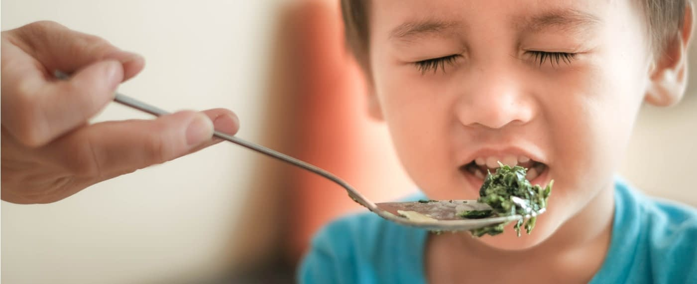 A child grimacing while being fed green vegetables
