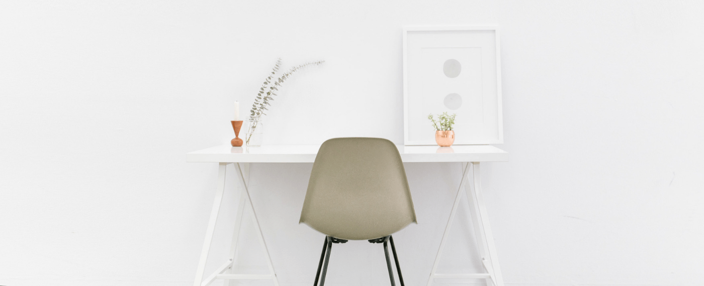 A minimalist white room with desk and chair
