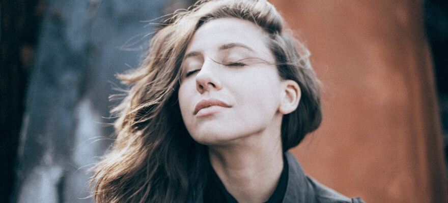 Brunette woman with her eyes closed hair in the wind