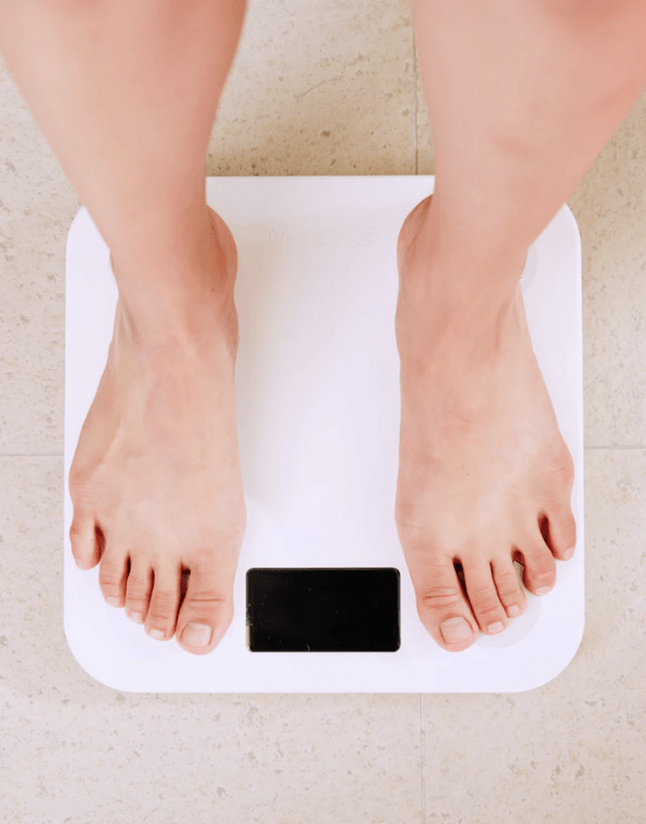 Bare feet standing on top of a scale used for measuring weight