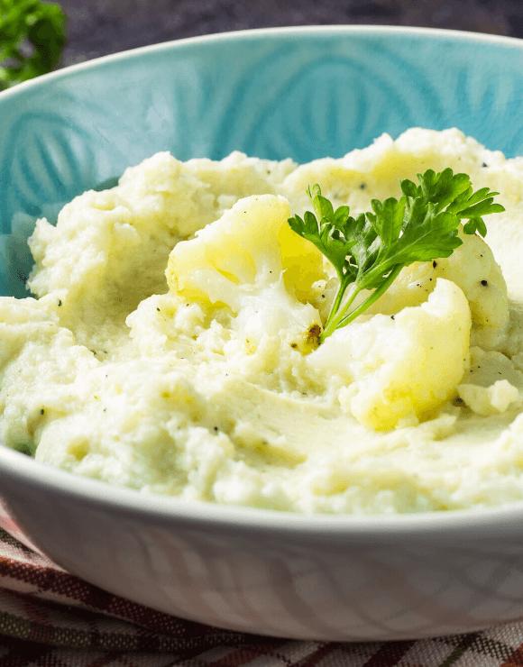 Vegan roasted garlic mashed cauliflower garnished with a piece of basil