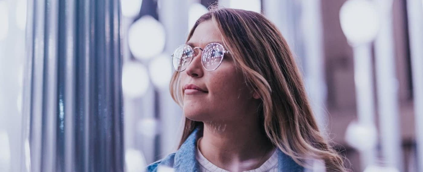 A young woman with glasses stares out of frame