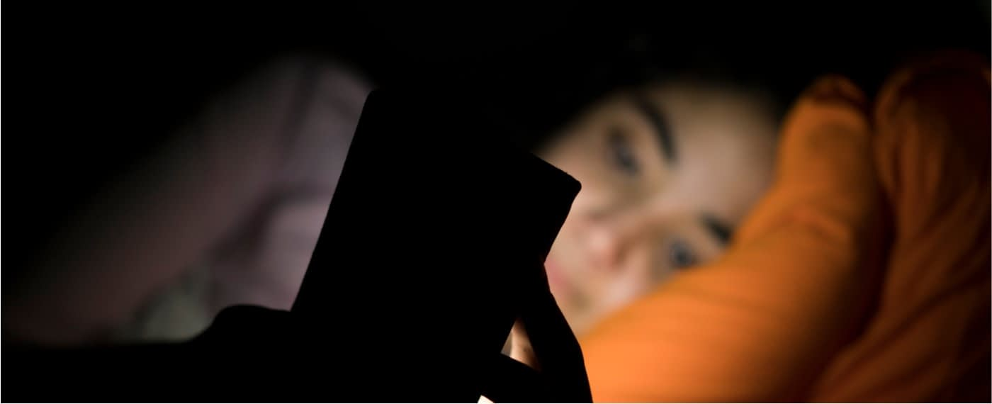 Girl looking at smartphone at night while lying in bed