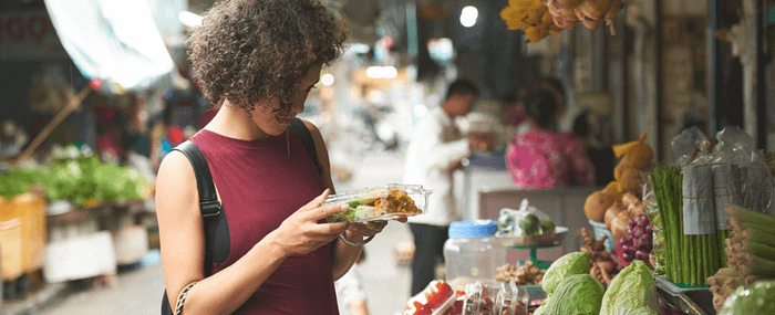 Woman carefully examining a container of food from a street market