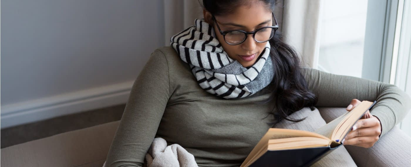 girl with glasses focusing on reading a book
