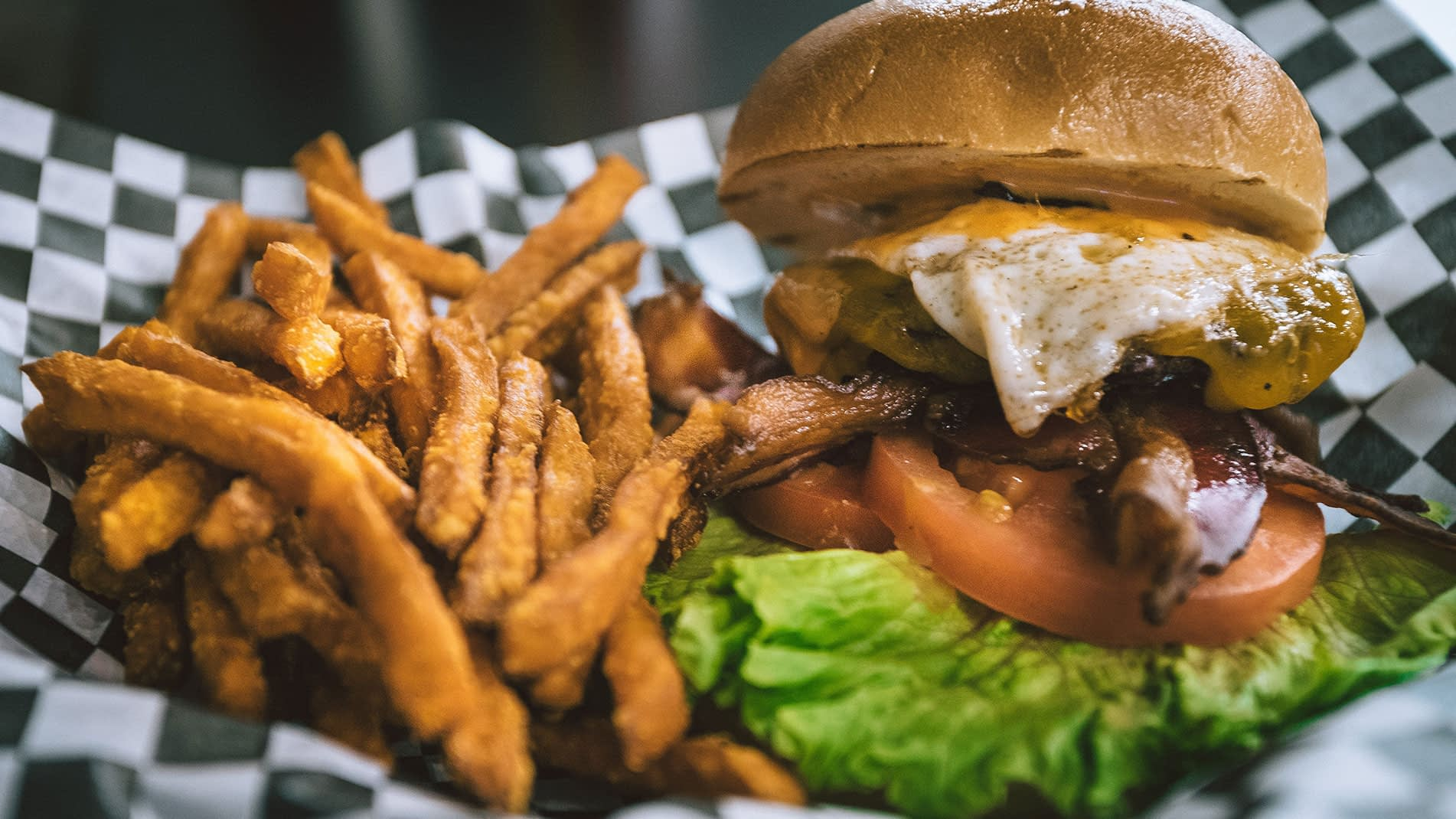 A greasy burger with fried egg and a side of fries