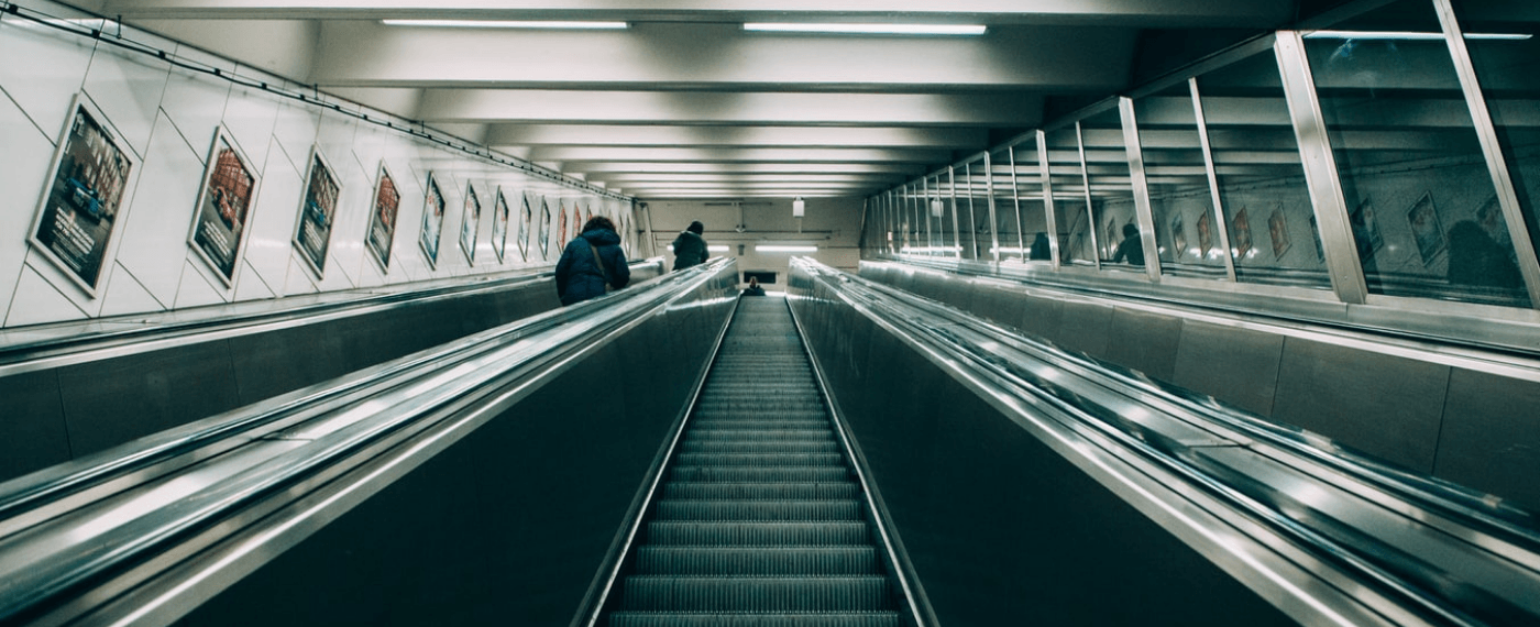 an image of a subway escalator stairs where the fluorescent lights causes headaches