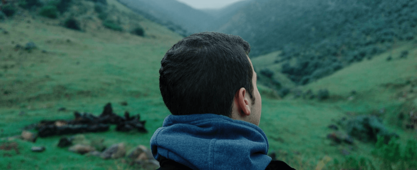 man staring out at green pastures thinking about the environment