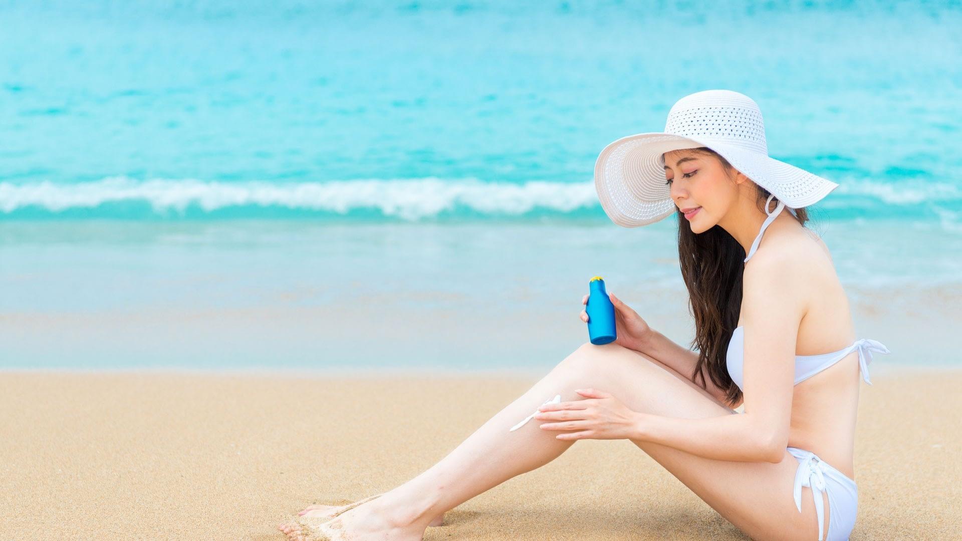 Lady on the beach applying korean sunscreen to her leg
