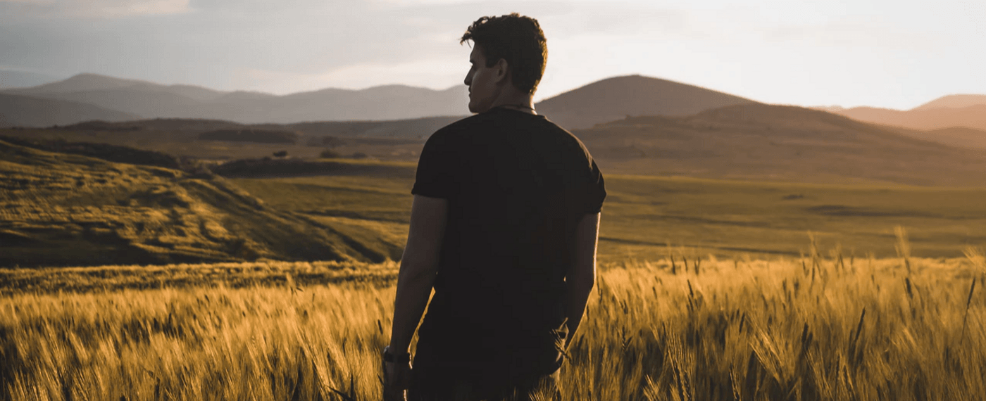 Man looking out over field of wheat and mountains