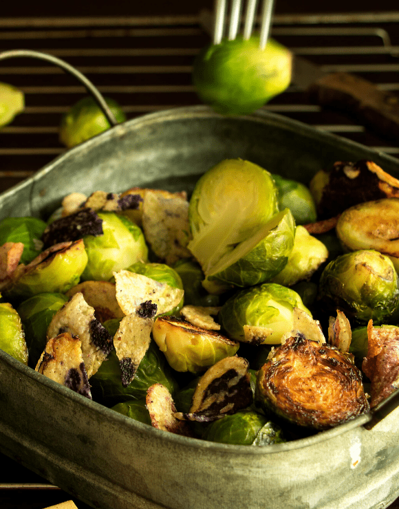 An iron skillet with roasted brussel sprouts with shallots and sunchokes