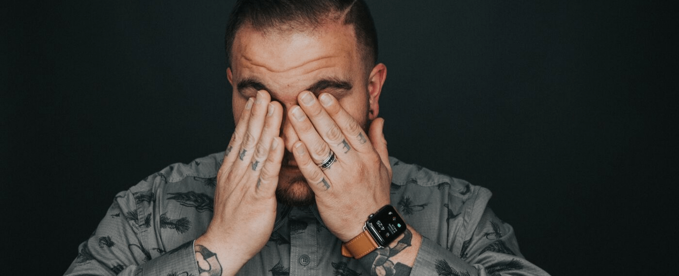 Man with tattoos suffering from a migraine covering his face