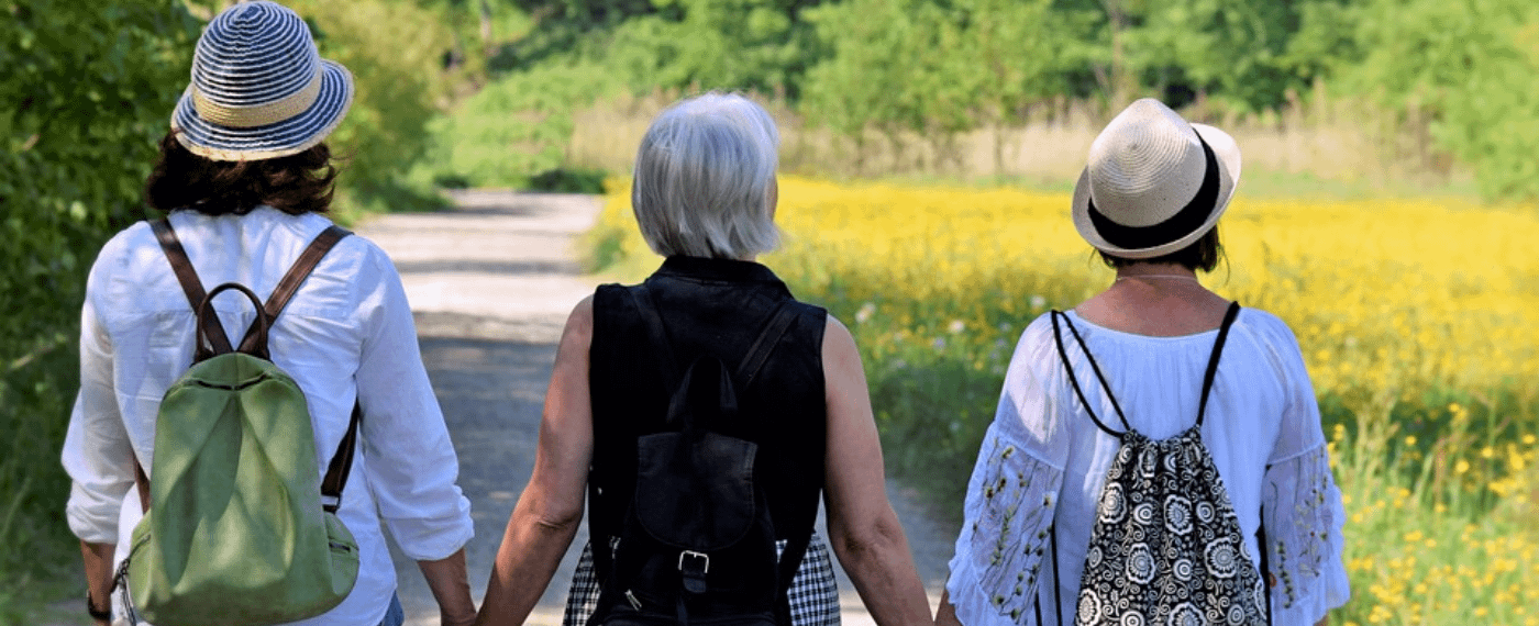 Three woman with perimenopause holding hands and walking