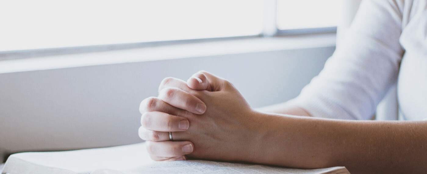Close up of man's hands resting on white linen