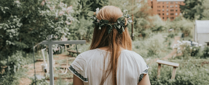 girl wearing a crown of leaves looks out at a field of wild flowers of bushes
