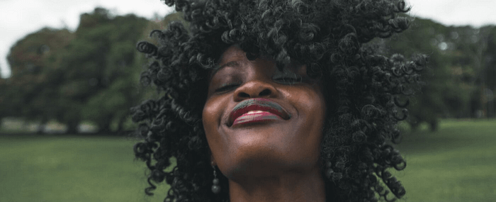 woman smiling with her eyes closed saying positive phrases to herself