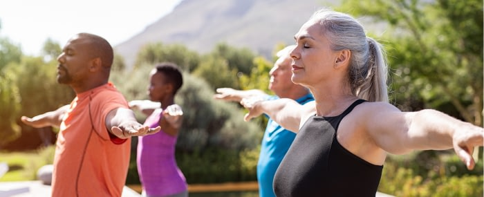 Older group of friends practicing breathing techniques to help reduce inflammation