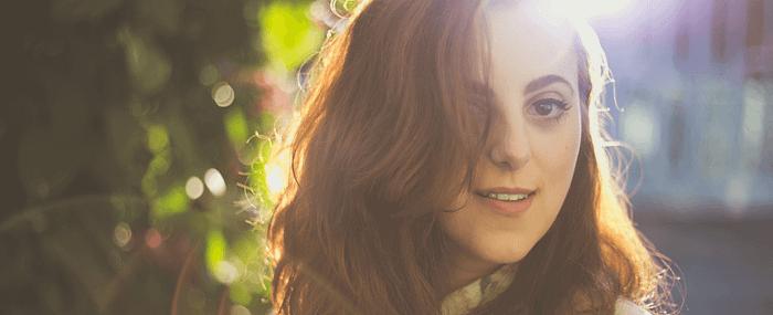 Woman with auburn hair outside in the sun