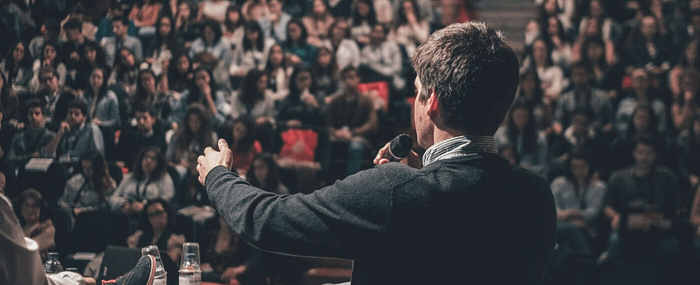 Over the shoulder shot of man speaking to a large crowd