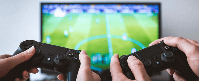 Two people holding video game controllers with TV in background