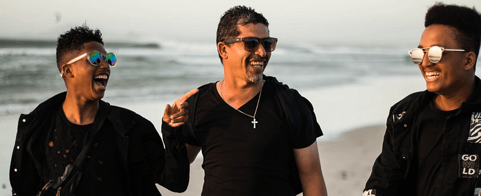 Group of three men wearing sunglasses, laughing on the beach