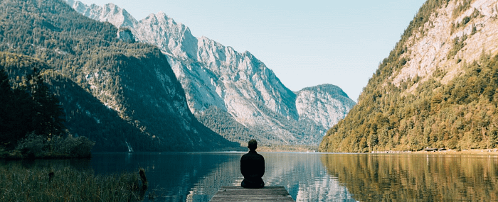Man sitting on the dock of a lake looking at mountains