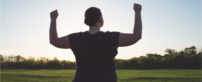Woman standing in a field with her arms raised in power