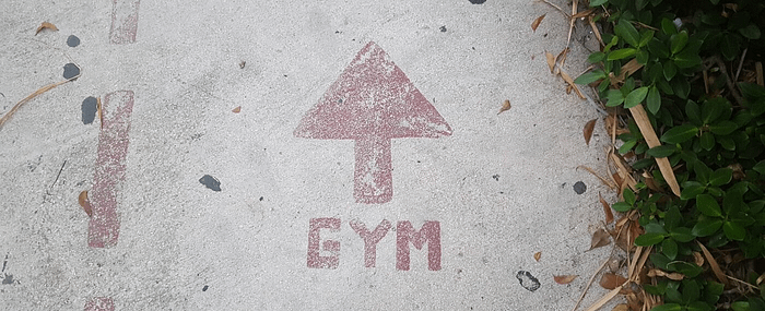 Directions to the gym painted on a sidewalk