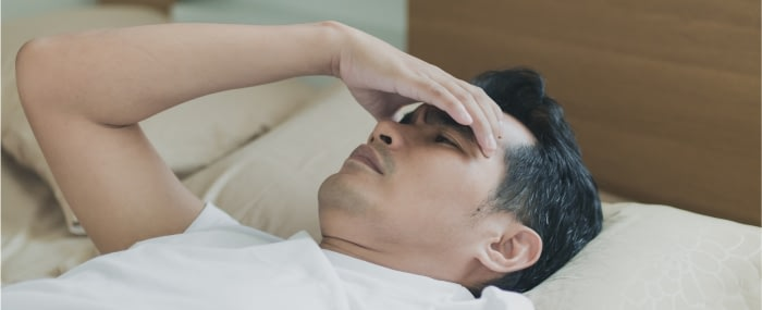Man laying in bed in pain