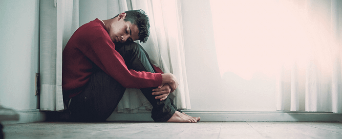 A young man huddled in a corner overwhelmed by anxiety