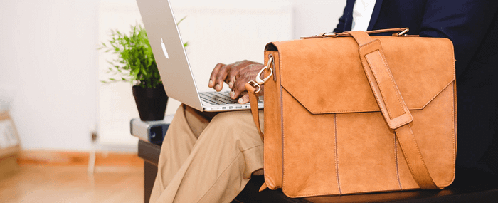 Man with suitcase and laptop working in a waiting room due to poor time management
