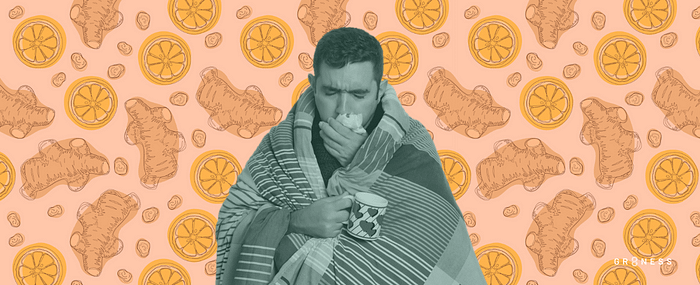 A man wrapped in a blanket coughing up phlegm into a tissue