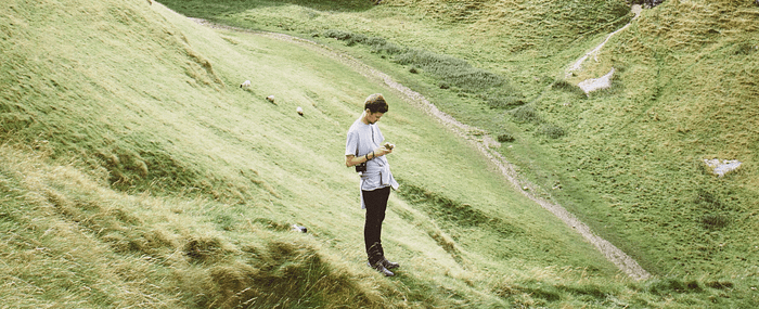 man in the middle of a green field scrolling through his cell phone