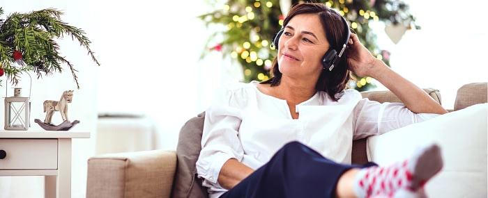 woman sitting outside enjoying music through headphones